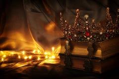 låg nyckel- bild av den härliga drottning-/konungkronan på den gamla boken medeltida period för fantasi arkivfoton