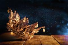 låg nyckel- bild av den härliga drottning-/konungkronan på den gamla boken medeltida period för fantasi Selektivt fokusera Royaltyfria Foton