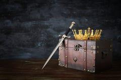 låg nyckel- bild av den härliga drottningen/det konungkronan och svärdet medeltida period för fantasi royaltyfri fotografi