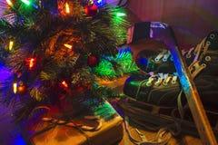 Låg nyckel- bild av en tänd julgran med skridskor och hockeypinnen Royaltyfri Fotografi
