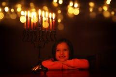 Låg nyckel- bild av judisk ferieChanukkahbakgrund med den gulliga flickan som ser menoror & x28; traditionell candelabra& x29; royaltyfri foto