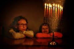 Låg nyckel- bild av judisk ferieChanukkahbakgrund med två gulliga ungar som ser traditionella kandelaber för menoror Royaltyfri Fotografi