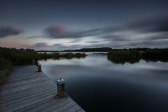 Låg nyckel- natt sjö i lång exponering Fotografering för Bildbyråer