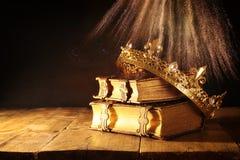 låg tangent av den härliga drottning-/konungkronan på gamla böcker Filtrerad tappning medeltida period för fantasi Arkivfoton
