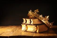 låg tangent av den härliga drottning-/konungkronan på gamla böcker Filtrerad tappning medeltida period för fantasi arkivbilder