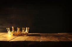 låg tangent av drottningen/konungkronan över trätabellen Filtrerad tappning medeltida period för fantasi Royaltyfri Foto