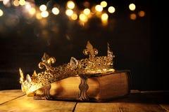 låg tangent av drottningen/konungkronan på den gamla boken Filtrerad tappning medeltida period för fantasi Royaltyfri Foto