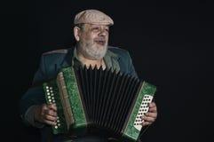 Låg tangent för stående av en gammal pensionerad militär man som sjunger, medan spela som är accordian Royaltyfri Foto