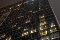 Låg vinkel av byggnad med exponeringsglasyttersida på bakgrund för natthimmel arkivbilder