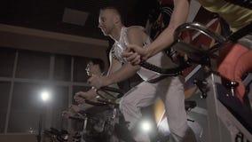 Låg-vinkeln sköt av tre konditionpersoner som utarbetar på idrottshallen stock video