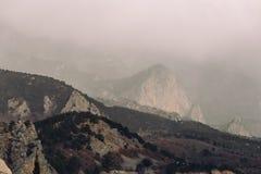 Låga liggande moln på berg i myst eller skymning, mörk dramatisk och för höst deprimerande atmosfär arkivfoto