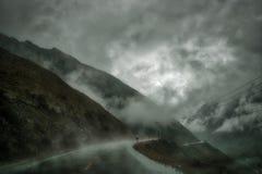 Låga moln i berg och våt asfaltväg arkivbilder