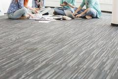 Lågt avsnitt av businesspeople som arbetar på golv i idérikt kontor Arkivfoton
