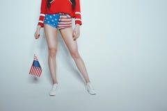 Lågt avsnitt av den stilfulla hipsterflickan i den amerikanska patriotiska dräkten som isoleras på grå färger Royaltyfri Bild