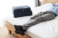 Lågt avsnitt av den unga affärsmannen som sover bredvid resväskan i hotellrum Arkivbild