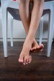 Lågt avsnitt av flickasammanträde på stol med korsade ben som dinglar över golv Arkivfoto
