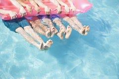 Lågt avsnitt av fyra vänner i ett pölinnehav på en uppblåsbar flotte med fot som klibbar ut ur vattnet Royaltyfria Bilder