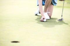 Lågt avsnitt av kvinnan som förlägger bollen på golfbanan royaltyfri foto