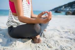 Lågt avsnitt av kvinnan som mediterar, medan sitta på sand på stranden Arkivbild