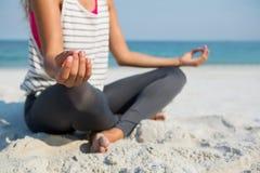 Lågt avsnitt av kvinnan som mediterar på stranden Fotografering för Bildbyråer
