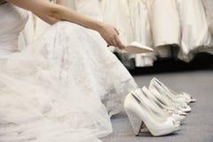 Lågt avsnitt av kvinnasammanträde med variation av skodon i brud- boutique royaltyfri bild