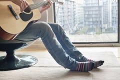 Lågt avsnitt av mannen som spelar gitarren royaltyfri bild