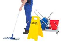 Lågt avsnitt av tjänaren som moppar golvet vid det våta golvtecknet Arkivbild