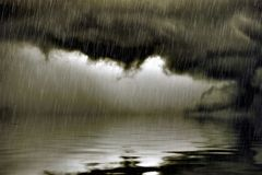 Lågt moln med regn över vatten Royaltyfri Bild