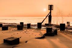 Lågvatten på soluppgång med vågen som sveper försiktigt över havsljumske Royaltyfri Foto