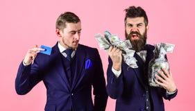 Lån- och bankrörelsebegrepp Män i dräkt, affärsmän med kruset som är full av kassa och kreditkort, rosa bakgrund Mogen man på royaltyfria bilder