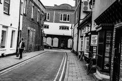 Låna ut kvinnan sett gå ner en öde sida-gata i en engelsk stad royaltyfri foto