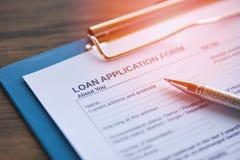 Lånansökningsblankett med pennan på papper/finansiell lånförhandling för långivare och låntagare royaltyfri bild