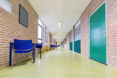 Lång övergiven korridor i skolabyggnad arkivfoto