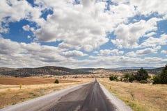 Lång asfaltväg med moln Arkivbild