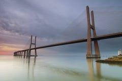 Lång bro över Tagus River i Lissabon på gryning Royaltyfria Bilder