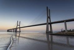 Lång bro över Tagus River i Lissabon på soluppgång royaltyfri bild