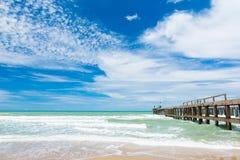 Lång bro på stranden med blå himmel Fotografering för Bildbyråer