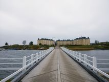Lång bro till ön med gamla hus Royaltyfri Bild