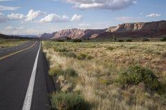Lång elasticitet av huvudvägen som leder av in i den sceniska höga öknen Royaltyfri Foto