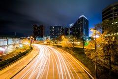 Lång exponering av byggnader och trafik på den ljusa gatan på natten, Royaltyfri Fotografi