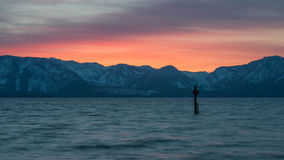 Lång exponering av den härliga Lake Tahoe solnedgången och snöig bergmaxima som tas från Nevada Beach, södra Lake Tahoe Arkivfoto