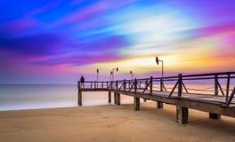 Lång exponering av färgrik soluppgång och träpir Royaltyfria Foton