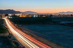 Lång exponering av ljusa slingor av bilar på en bygdväg royaltyfri bild