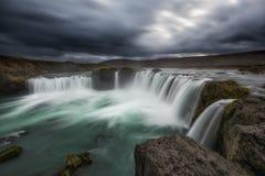 Lång exponering av mörker fördunklar över den Godafoss vattenfallet i Icealnd Royaltyfri Foto