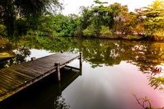 Lång exponering av pir i den lugna sjön, med naturen lite varstans, vatten är silkeslent slätt kulört ljus läcker på sidorna Royaltyfri Bild