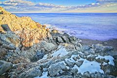 Lång exponering av snöig och stenigt förbiser av havet och kusten under vinter royaltyfri bild
