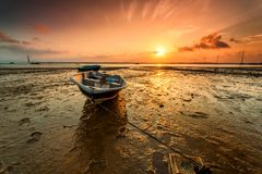 Lång exponeringsbild av fiskebåten med guld- solnedgång som lodisar Arkivfoto