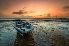 Lång exponeringsbild av fiskebåten med guld- solnedgång som lodisar Arkivbild