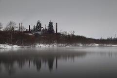 Lång exponeringsbild av industrianläggningen nära dammet med ånga på Arkivfoto