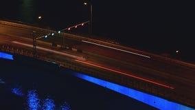 lång för statisk elektricitettid för exponering 4K schackningsperiod av billjus som på flyttar bron över floden på nattetid arkivfilmer
